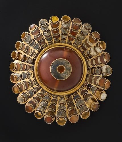 Eine runde Scheibe aus Gold mit vielen Edelsteinen besetzt.